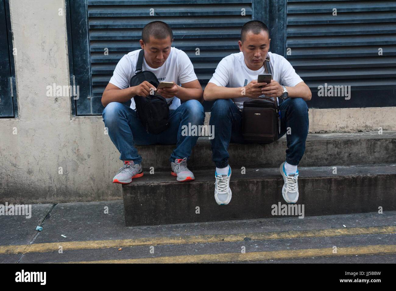 16.07.2017, Singapore, Republic of Singapore, Asia - Two men are occupied with their smartphones in Singapore's - Stock Image