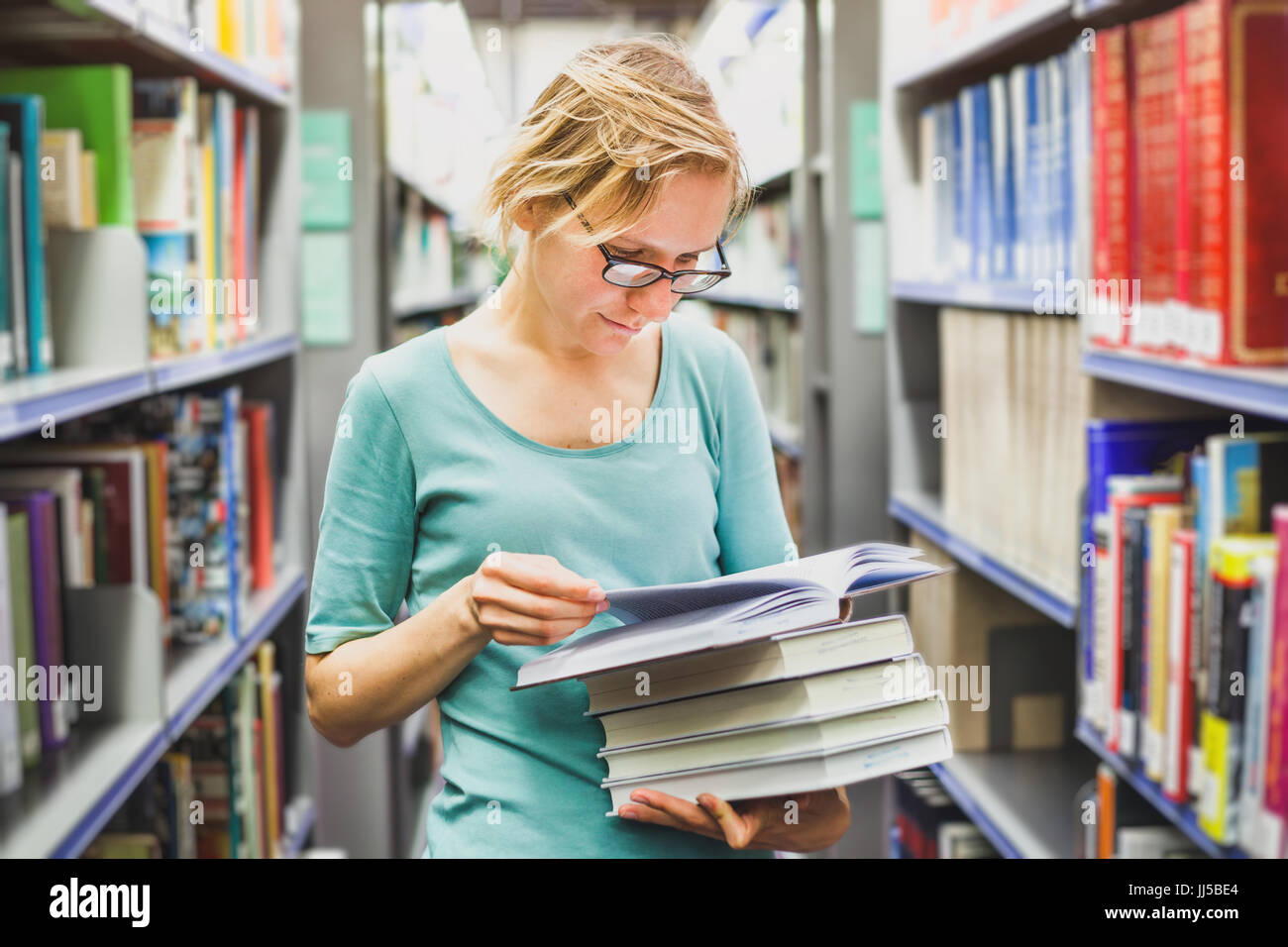 student girl in the library reading books, education concept - Stock Image