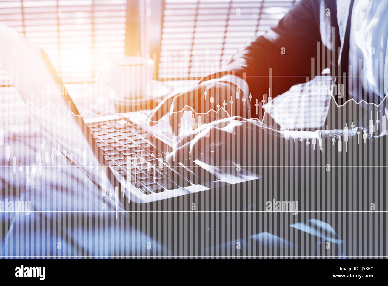 financial charts and graphics of interest rates and quotations, business man writing report on computer - Stock Image
