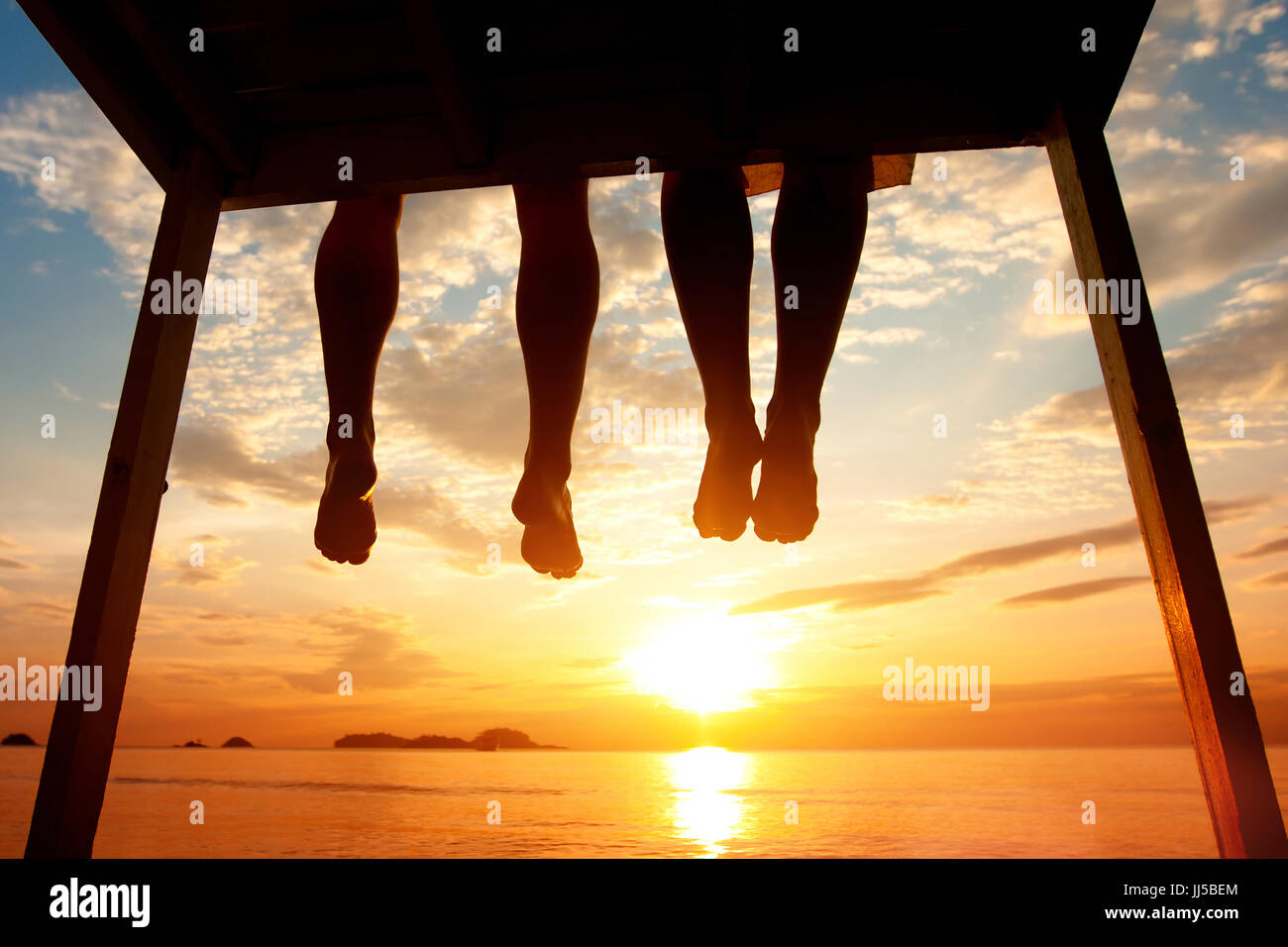 happiness concept, silhouette of feet of couple sitting on the pier at sunset beach - Stock Image