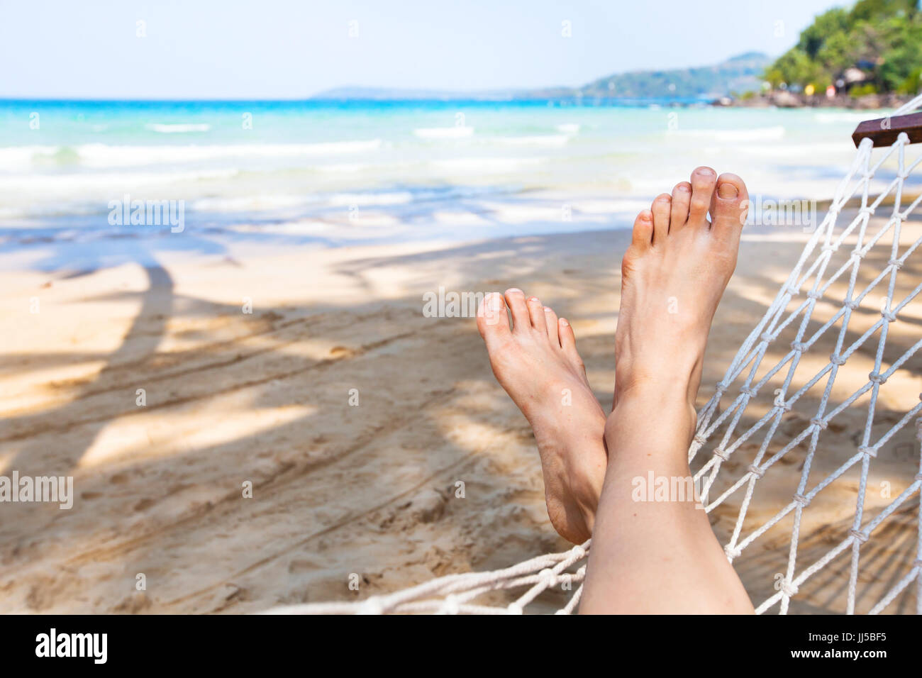beach holidays background, vacation and relaxation concept, feet of person in hammock - Stock Image