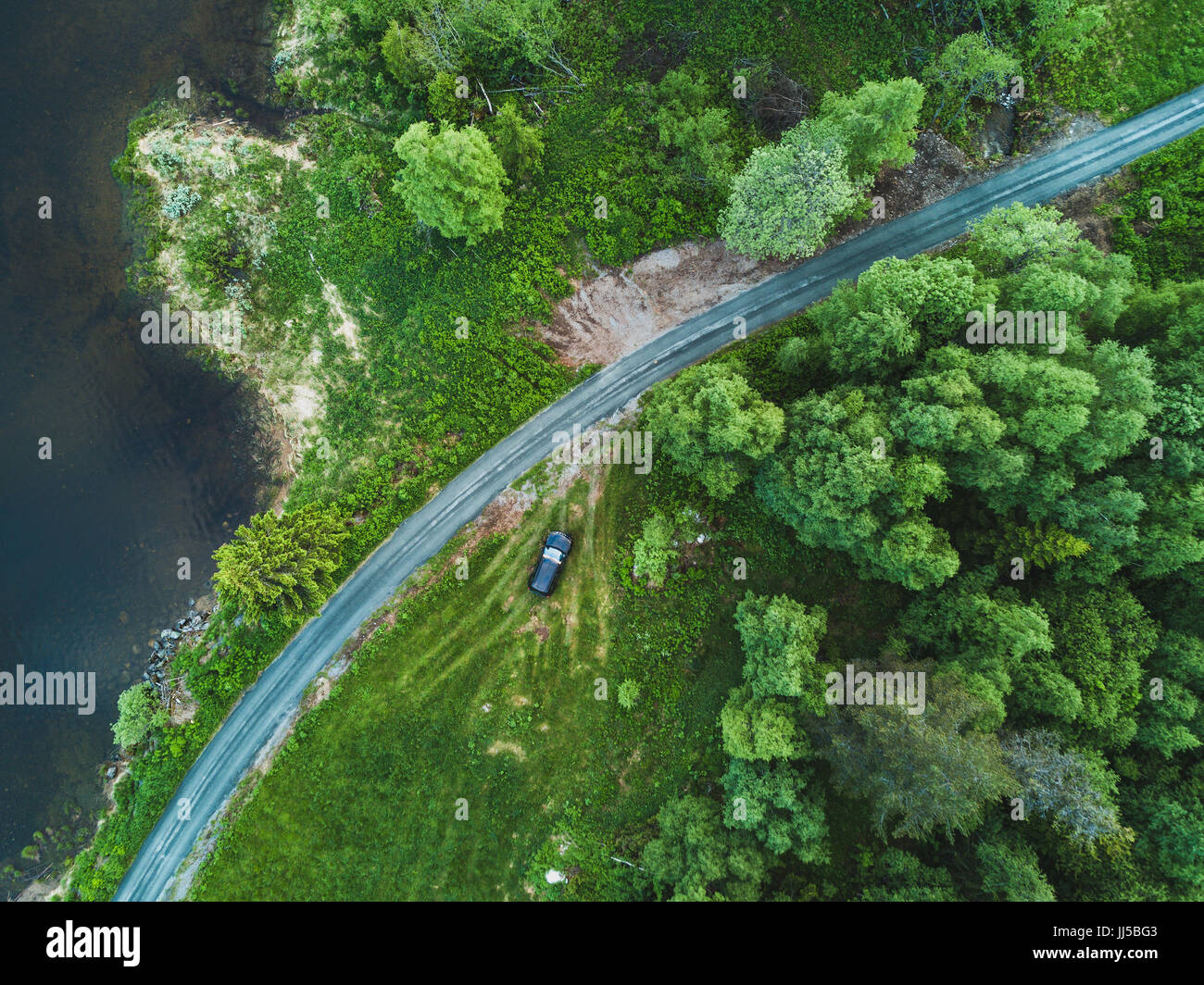 beautiful aerial view of countryside road in green forest, landscape from drone - Stock Image