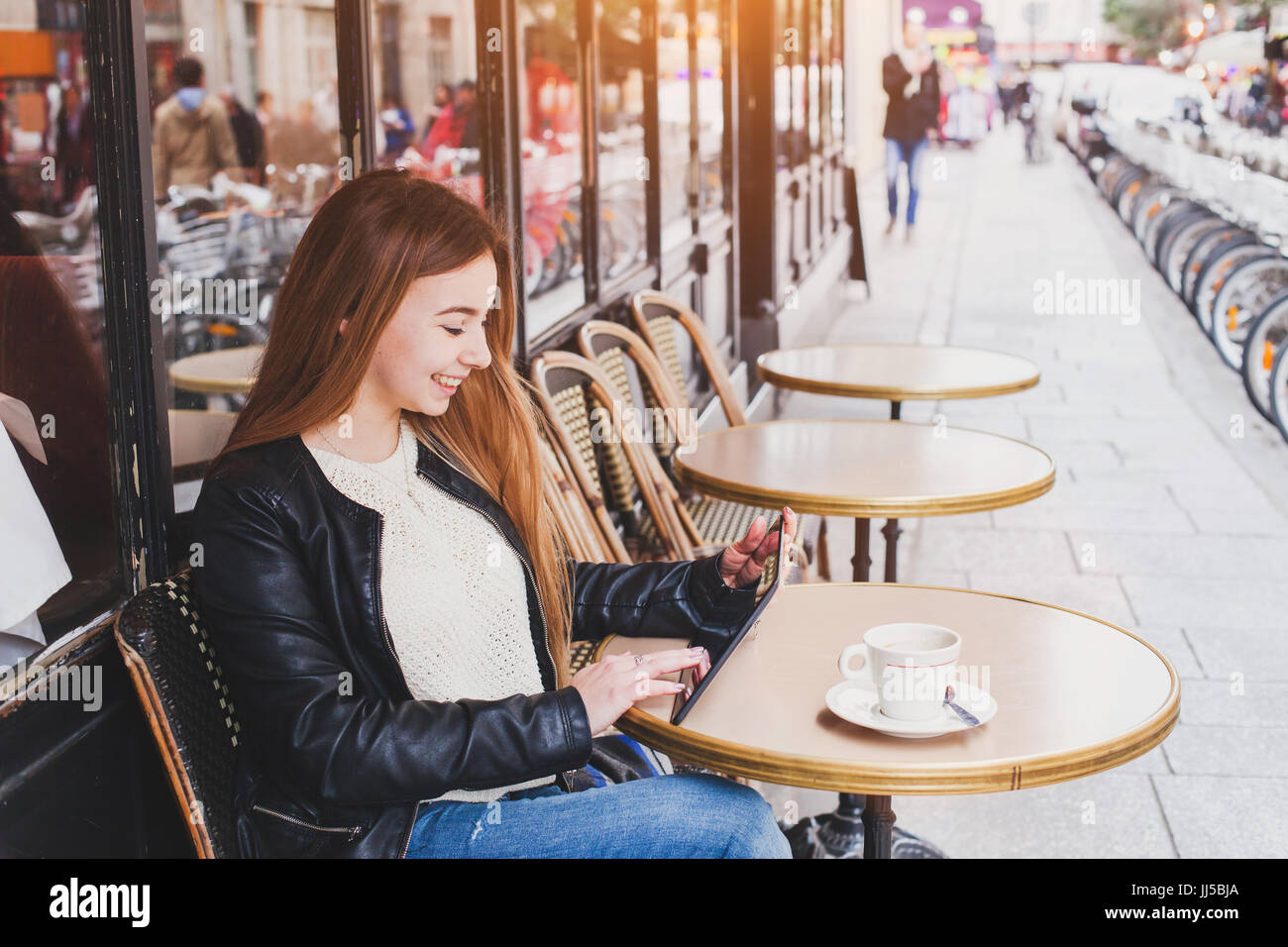 young woman using digital tablet computer in street cafe in Europe - Stock Image