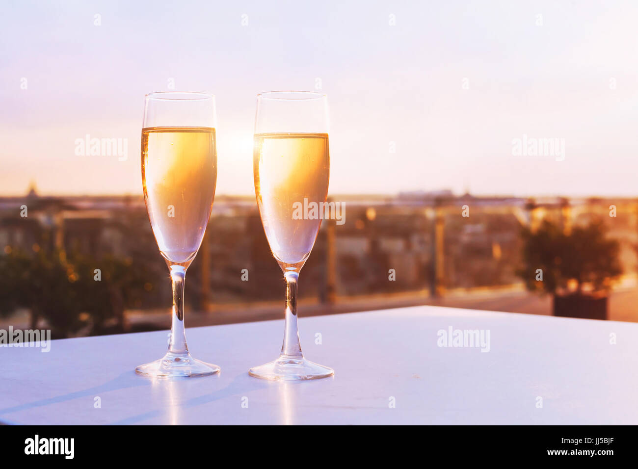 two glasses of champagne at rooftop restaurant with view of city skyline, luxury romantic dinner for couple - Stock Image