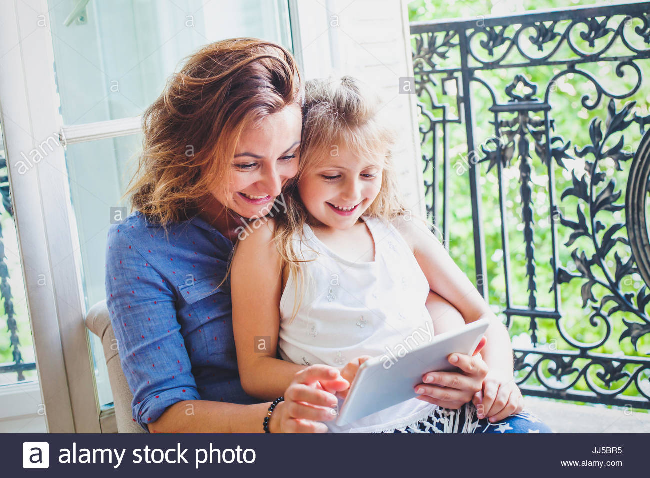 happy mother and daughter looking at digital tablet computer and smiling at home, shopping online - Stock Image