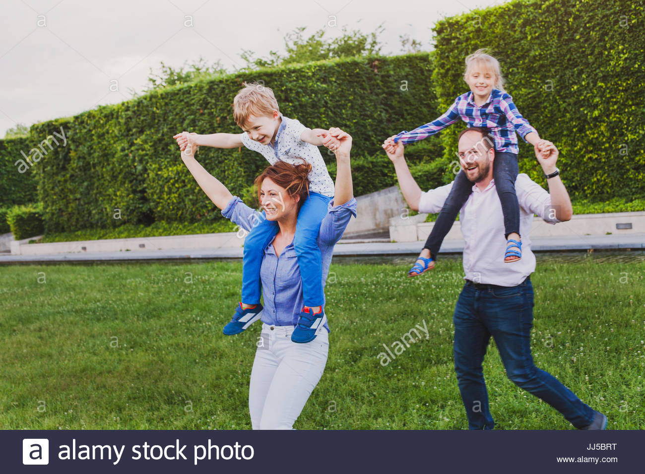 parents playing with children outside, happy family having fun in the park - Stock Image