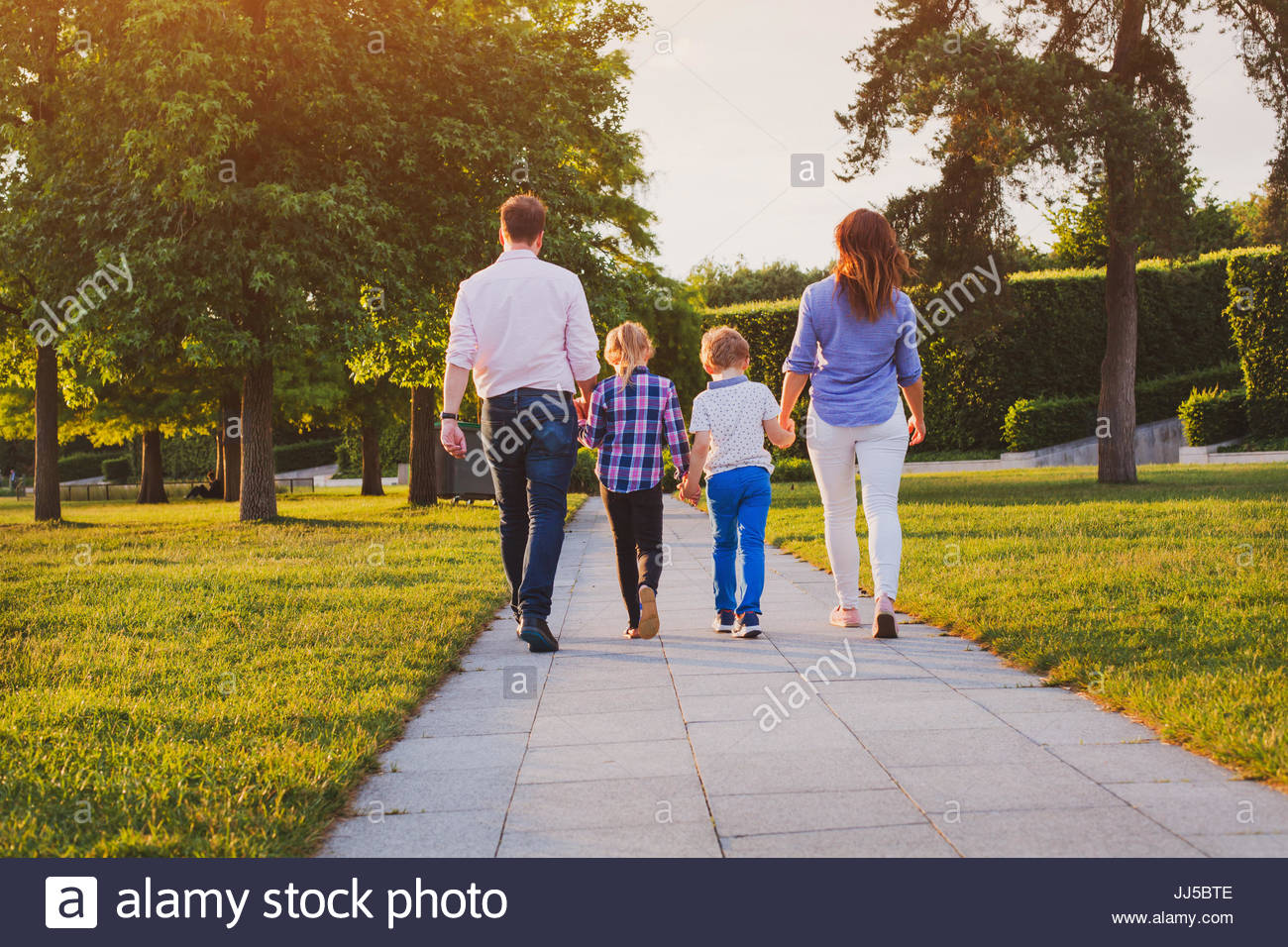 family with two kids walking in the park together at sunset, parents with children, view from the back - Stock Image
