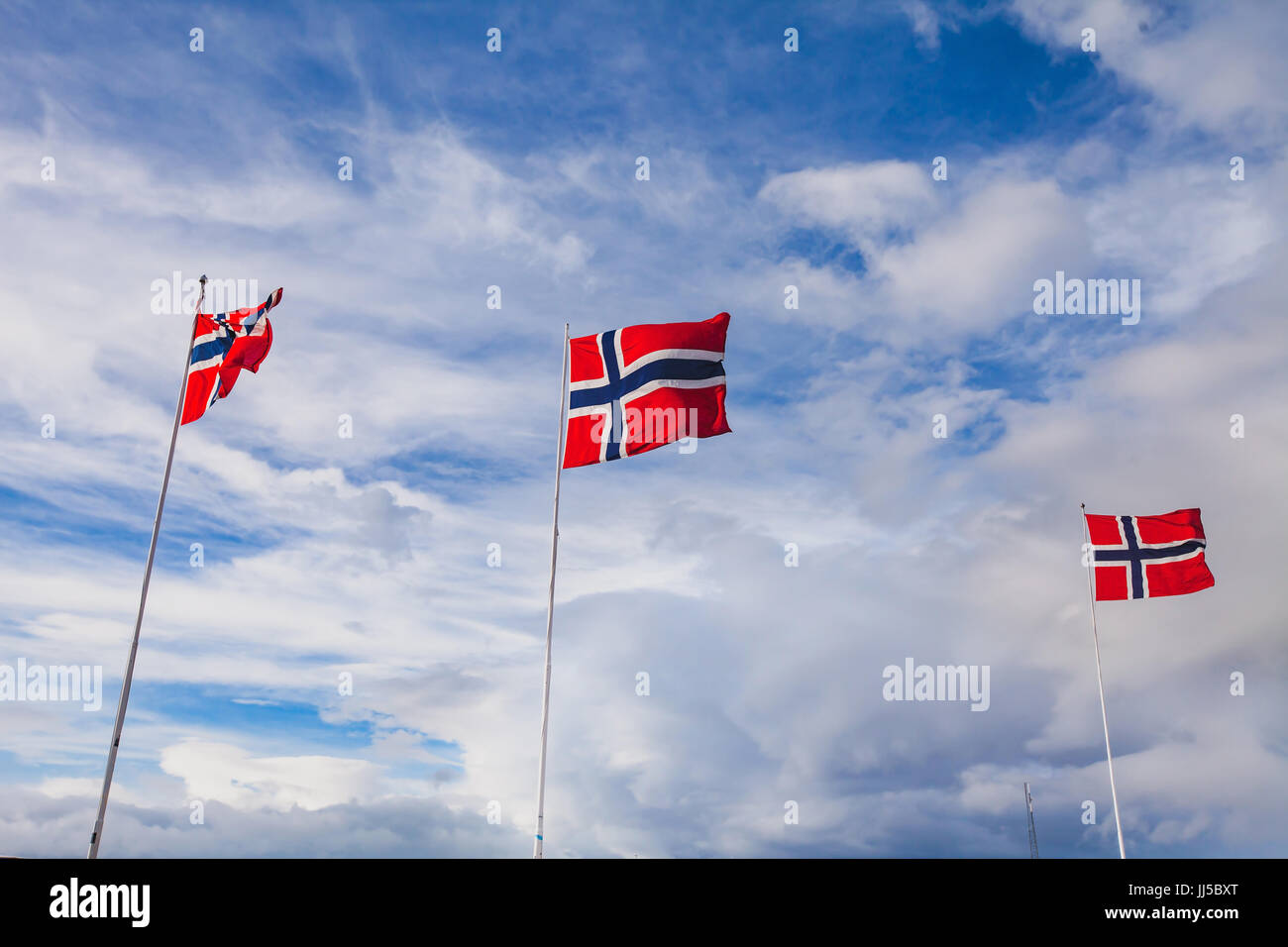 Norway, norwegian flags waving on blue sky background - Stock Image