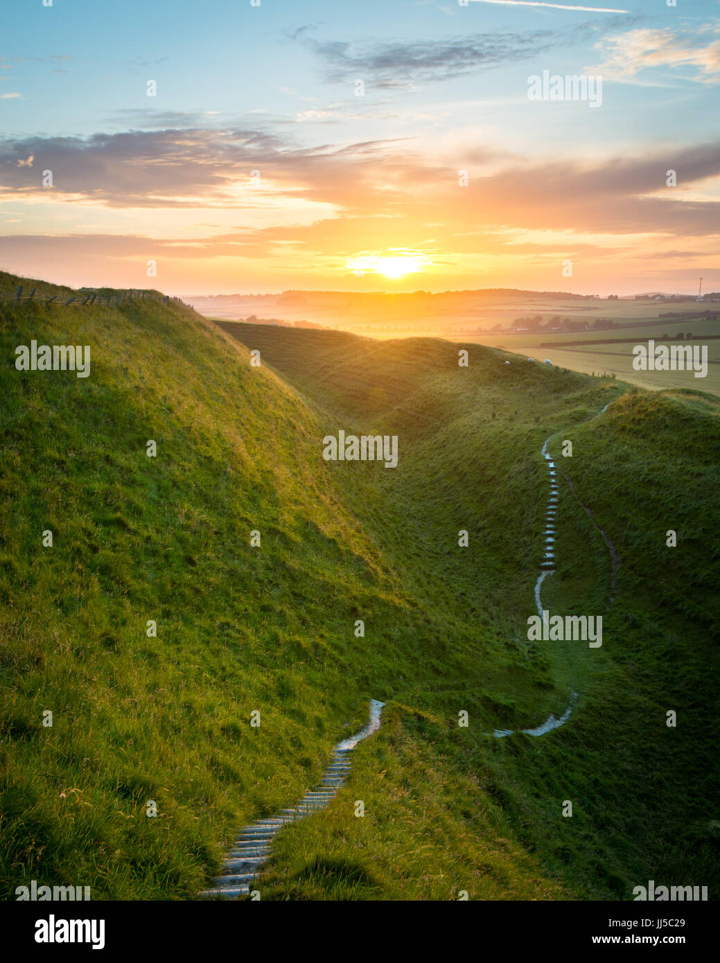 Footpath meanders through Maiden Castles huge ramparts as the sun set in the distance near Dorchester, Dorset, UK Stock Photo