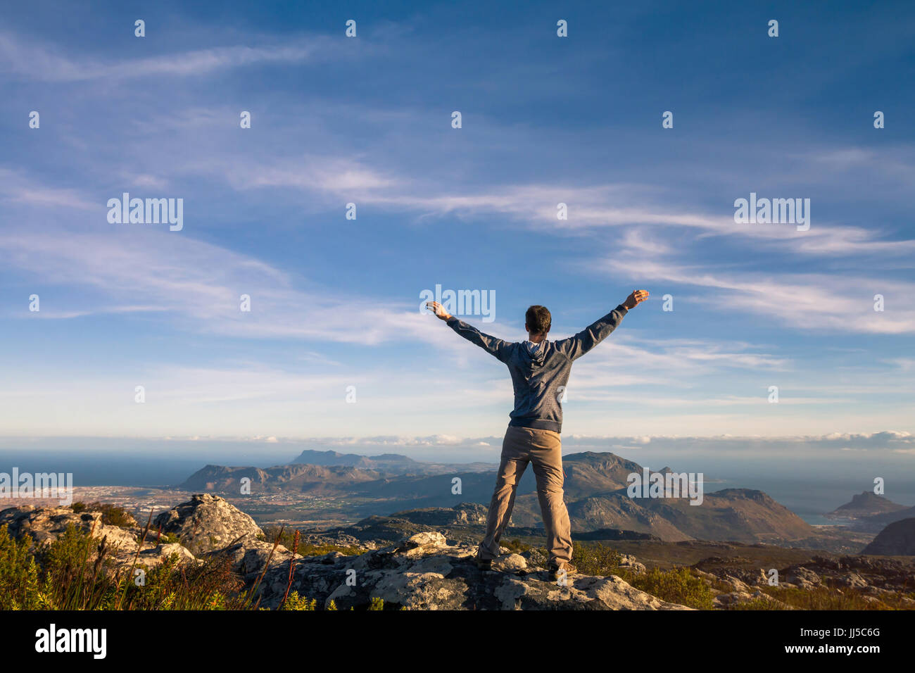 man standing with raised hands on top of Table mountain in Cape Town, South Africa - Stock Image