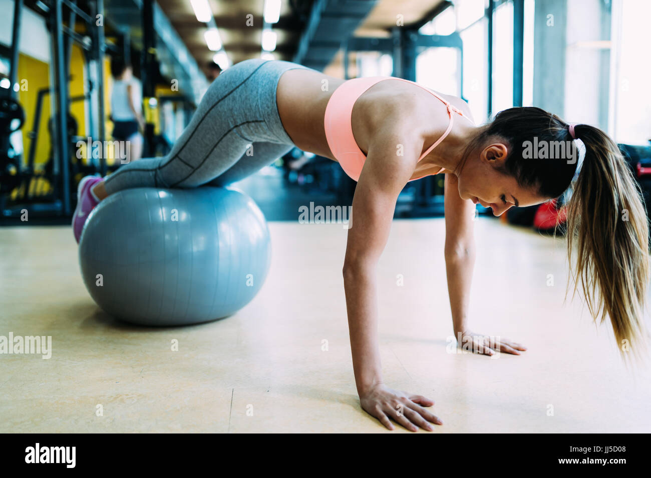 Fitness woman working push ups in gym - Stock Image