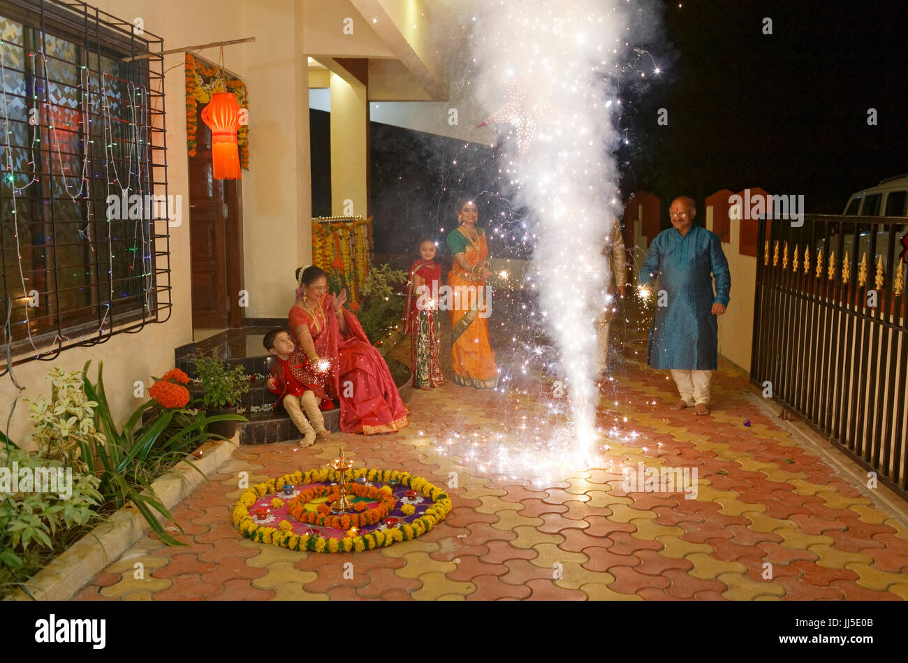 Indian family in traditional outfits celebrating Diwali or deepavali, festival of lights at home. - Stock Image