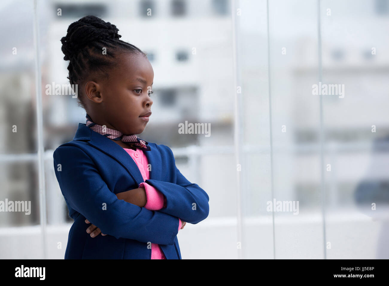 Contemplated businesswoman with arms crossed standing by glass window in office - Stock Image