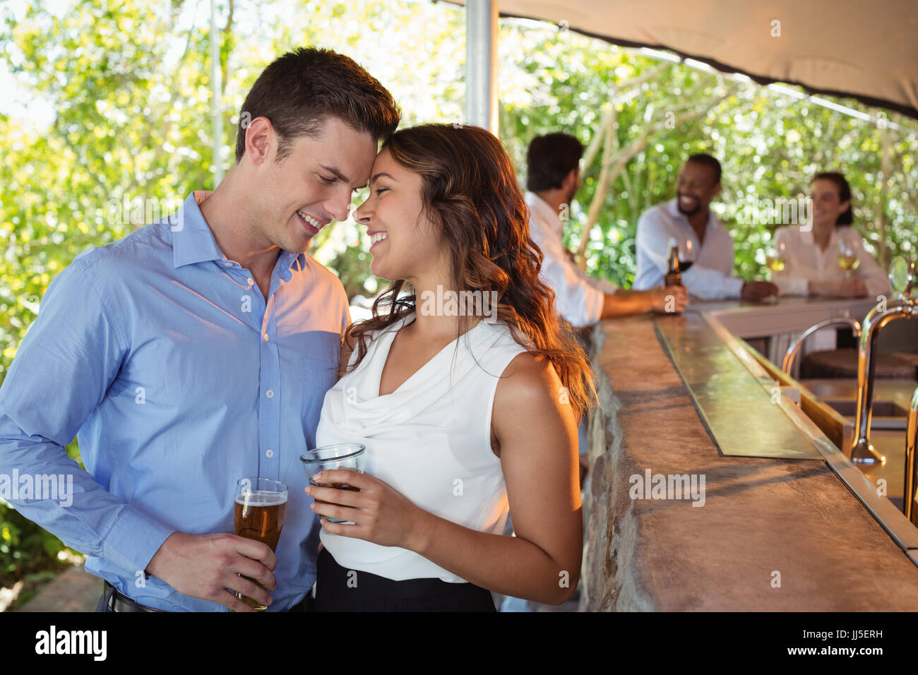 Romantic couple having a glass of beer at counter in restaurant - Stock Image