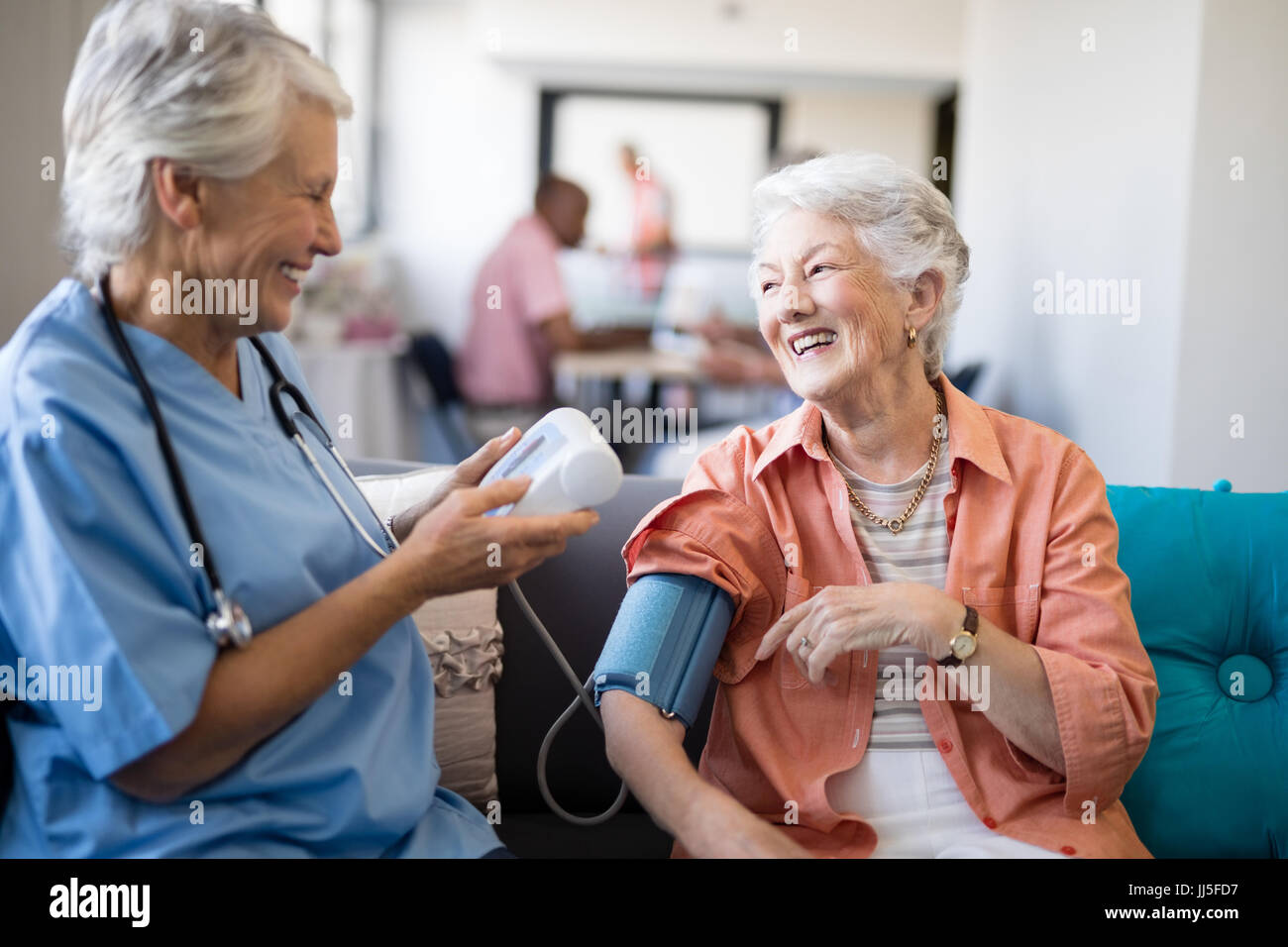 Smiling senior woman talking to female doctor during blood pressure check up at nursing home - Stock Image