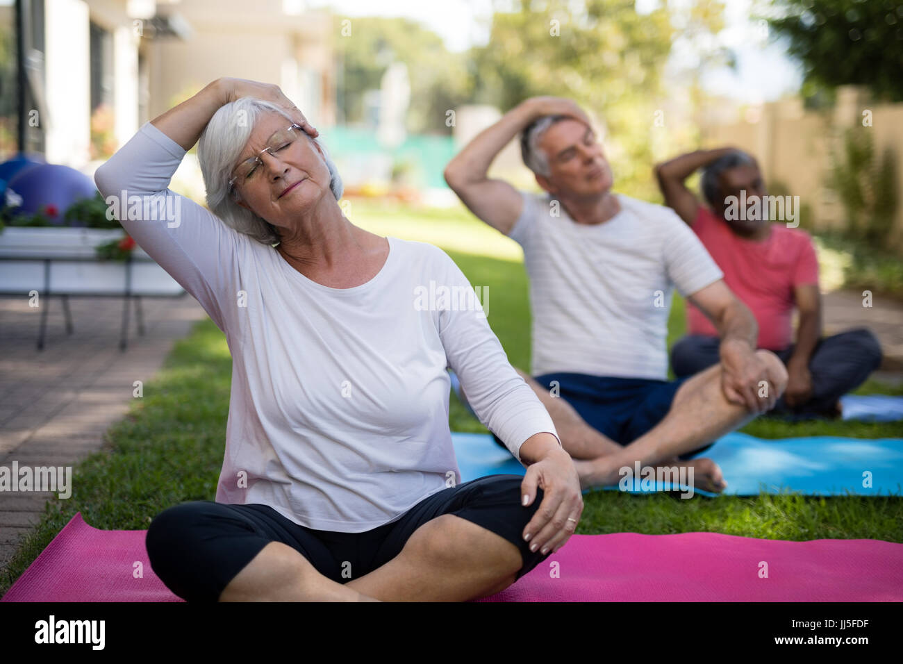 Senior people stretching heads while sitting on exercising mats at park - Stock Image