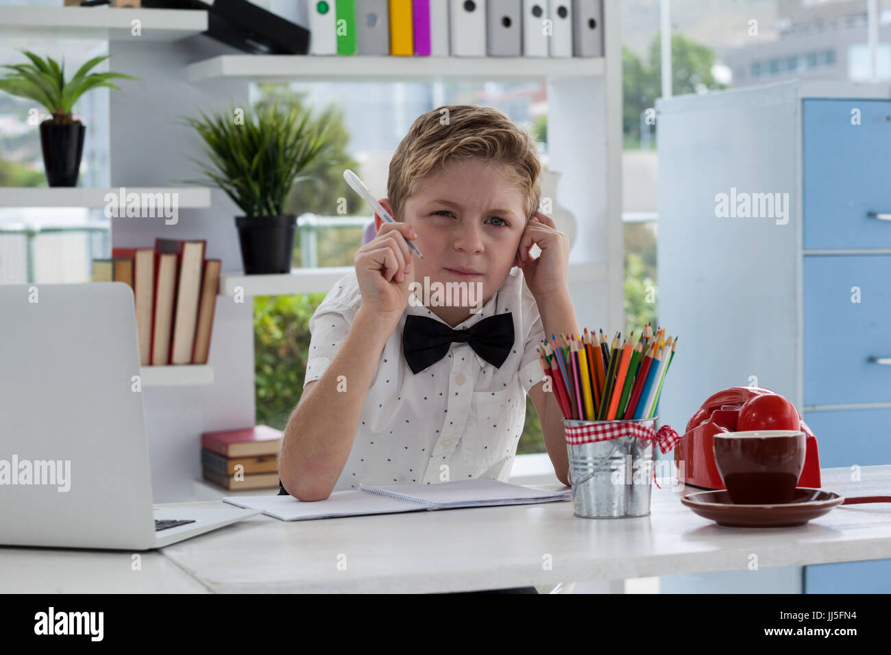 Businessman thinking while making report by laptop at desk in office - Stock Image