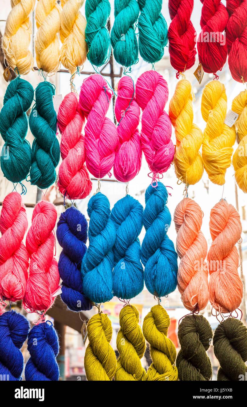 Bundles of yarn hang outside a shop i varanasi, Uttar Pradesh, India. - Stock Image