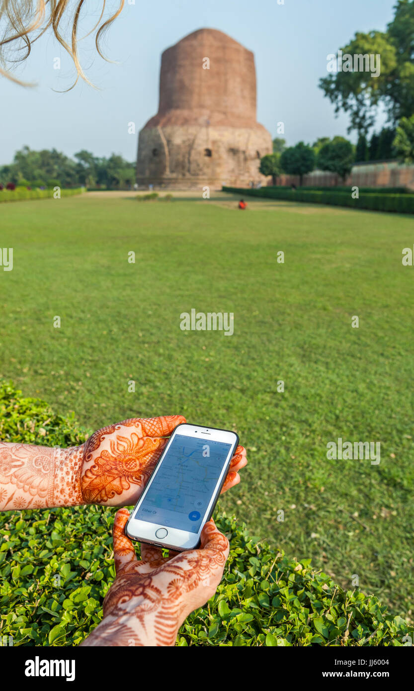 A woman's decorated hands hold a iPhone showing a map with Dhamekh Stupa in Sarnath, India in the background. - Stock Image