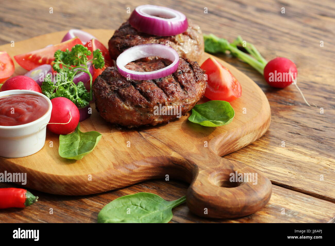Homemade beef burger with onion on cutting board - Stock Image