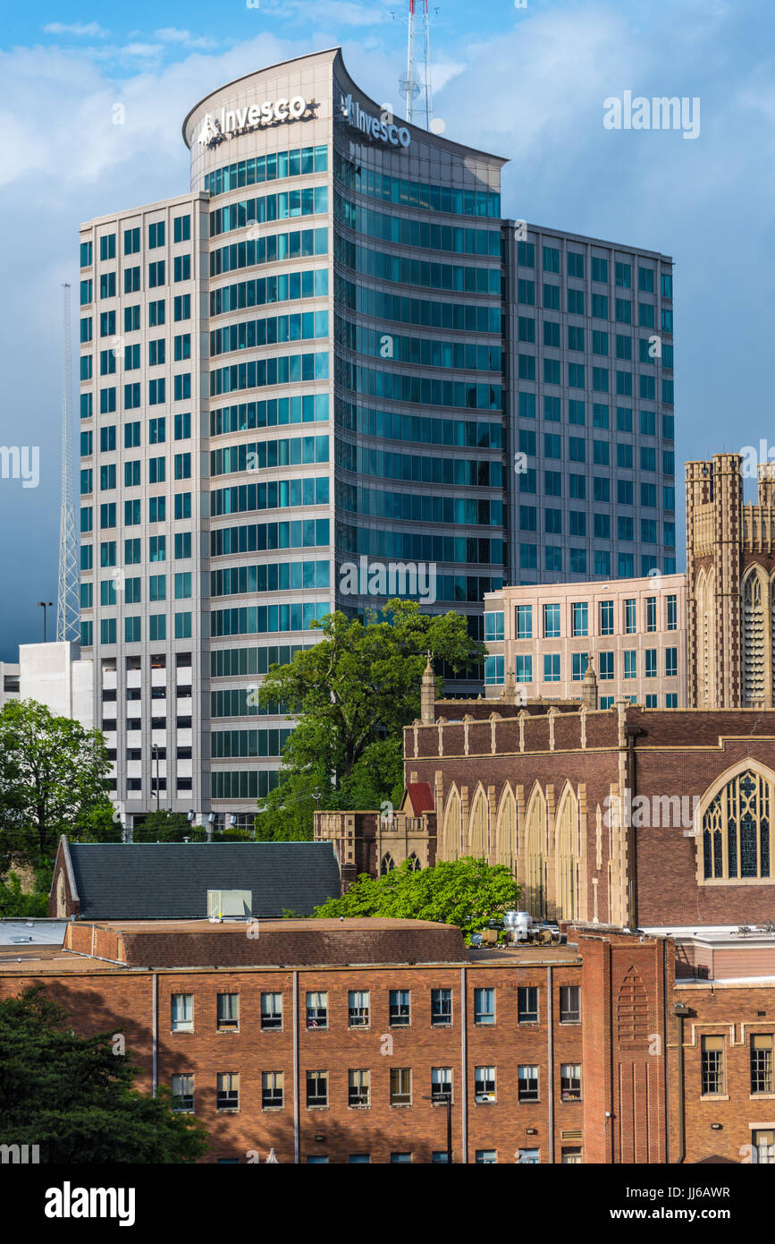 The modern glass Invesco building towers above the historic architecture of Peachtree Christian Church along Peachtree - Stock Image