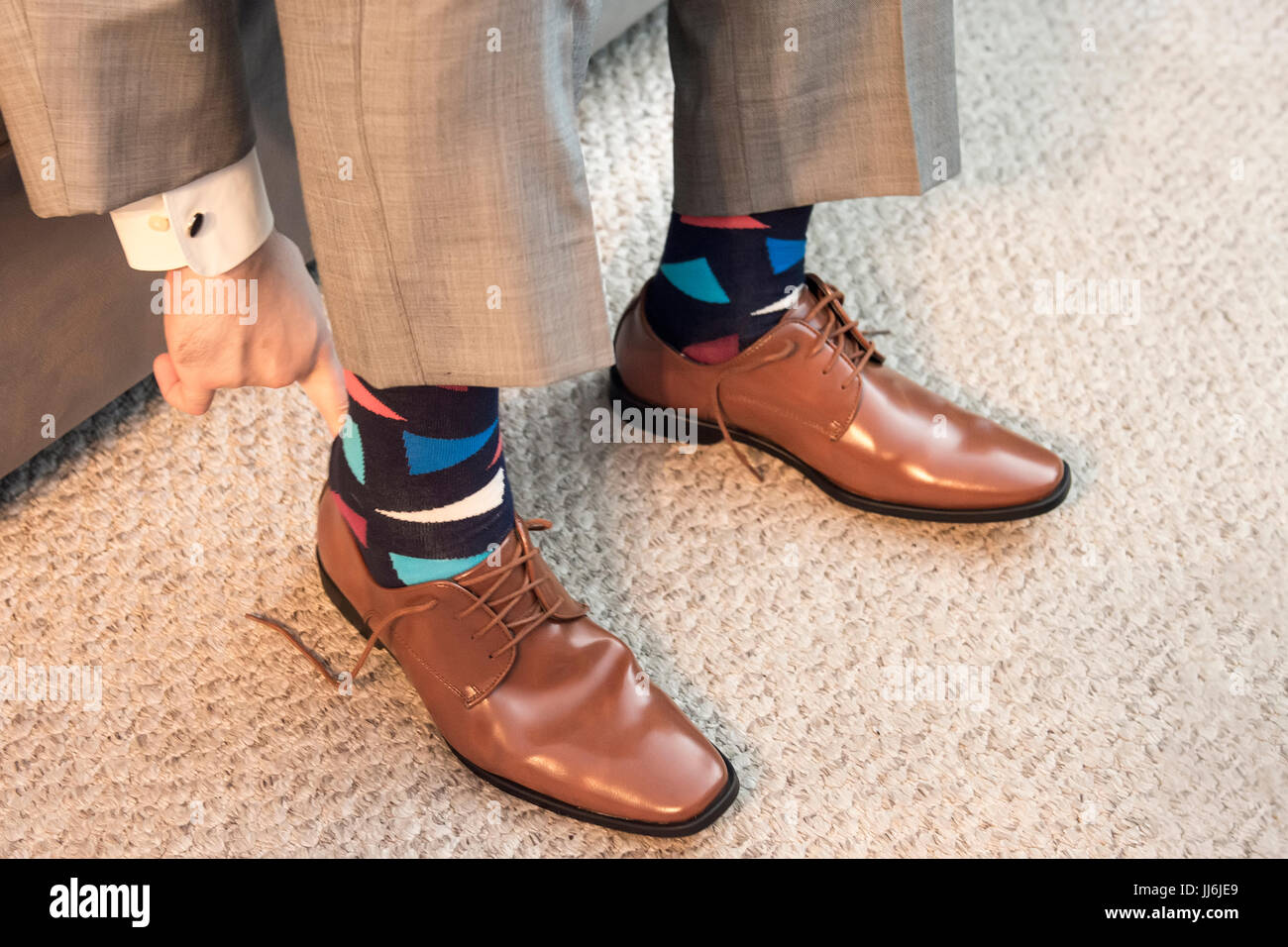 Man putting on brown dress shoes in formal wear with colorful socks for wedding - Stock Image