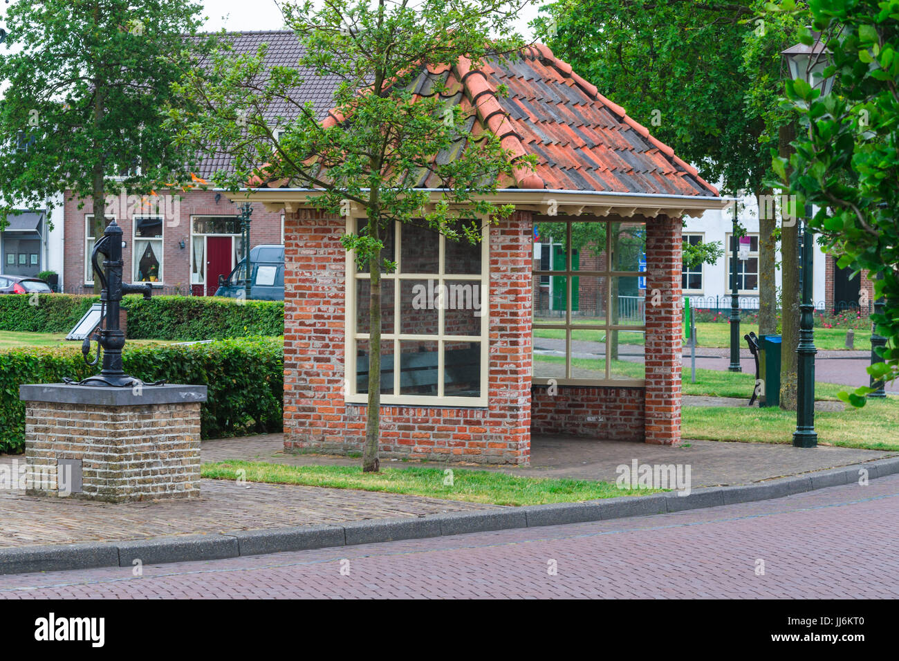 Bus stop of brickstone and old water pump in the Netherlands Renesse. - Stock Image