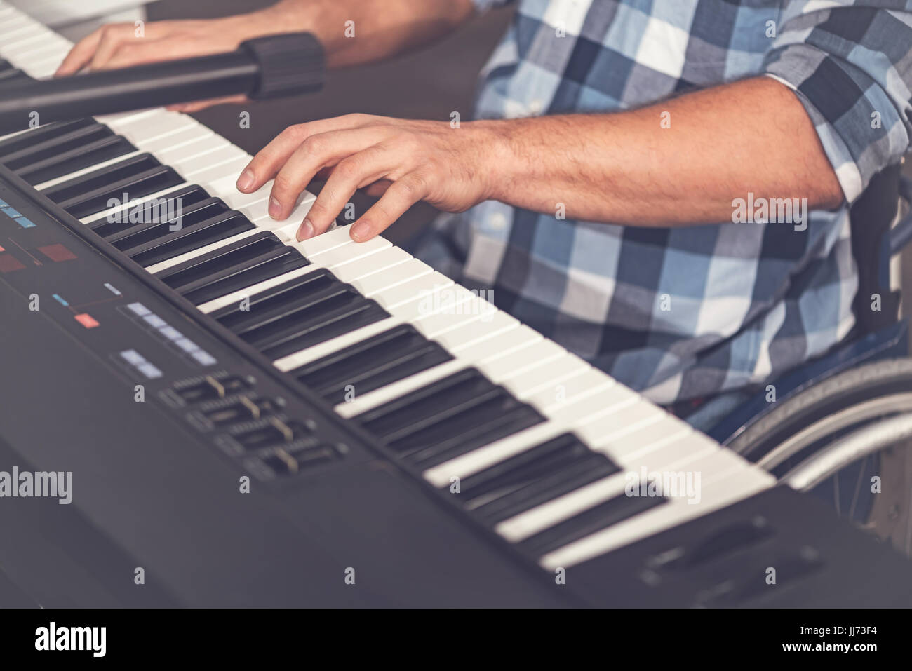 Close up of male hands while playing on electric piano - Stock Image