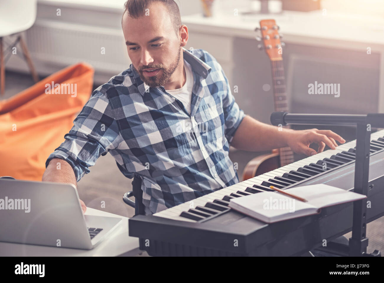 Confident accomplished musician using his laptop - Stock Image
