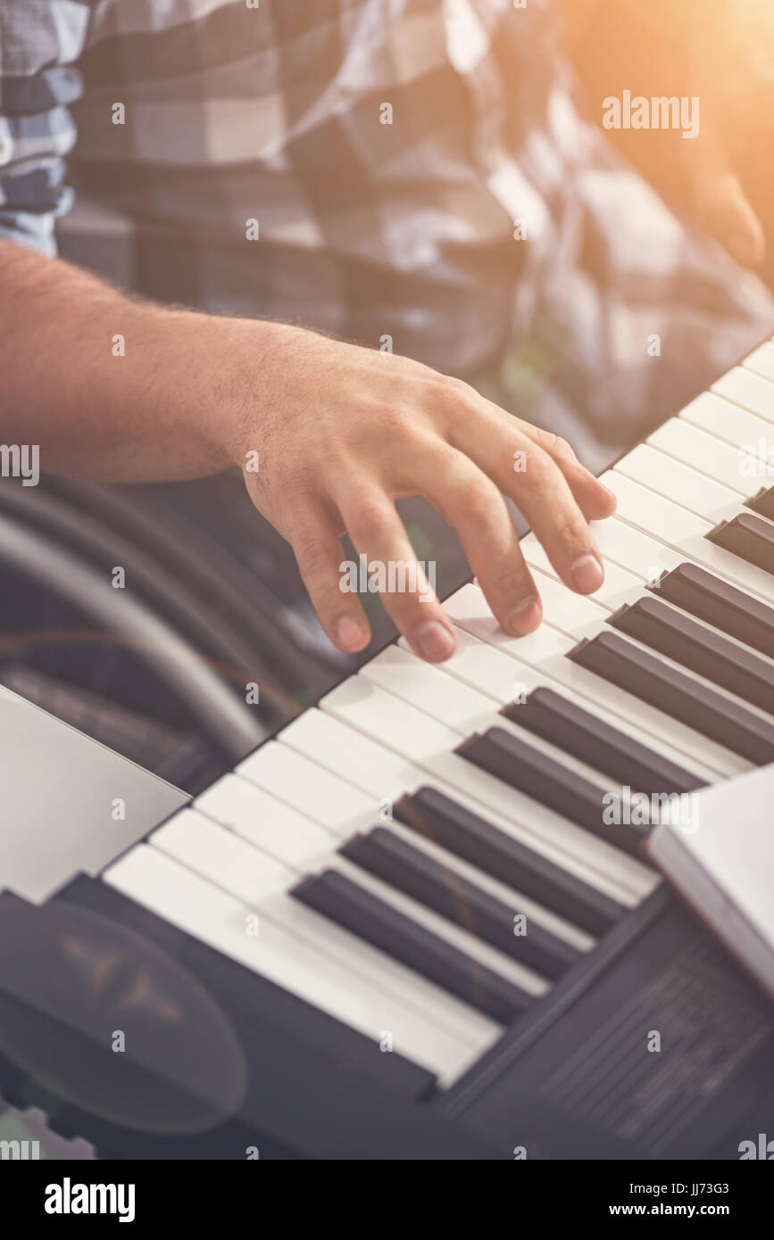 Male fingers playing the electric piano - Stock Image