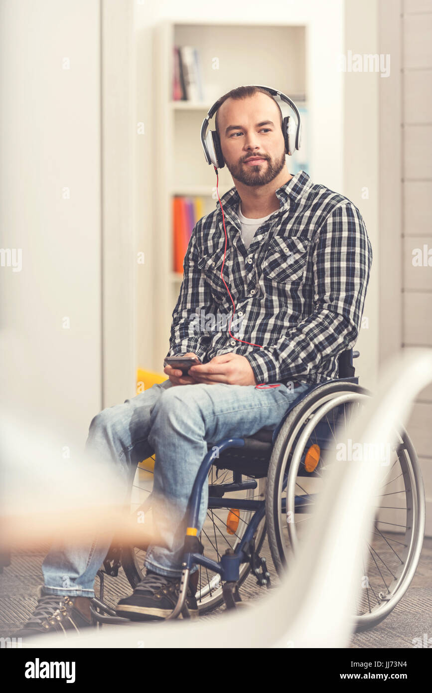Disabled young man listening to radio - Stock Image