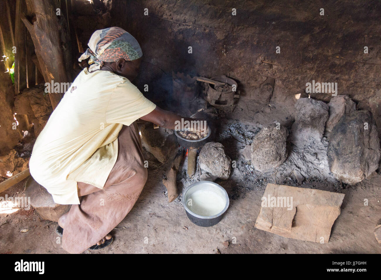An old black Ugandan woman cooking in metal pots on charcoal fire in a primitive outdoor kitchen in Buikwe, Uganda - Stock Image