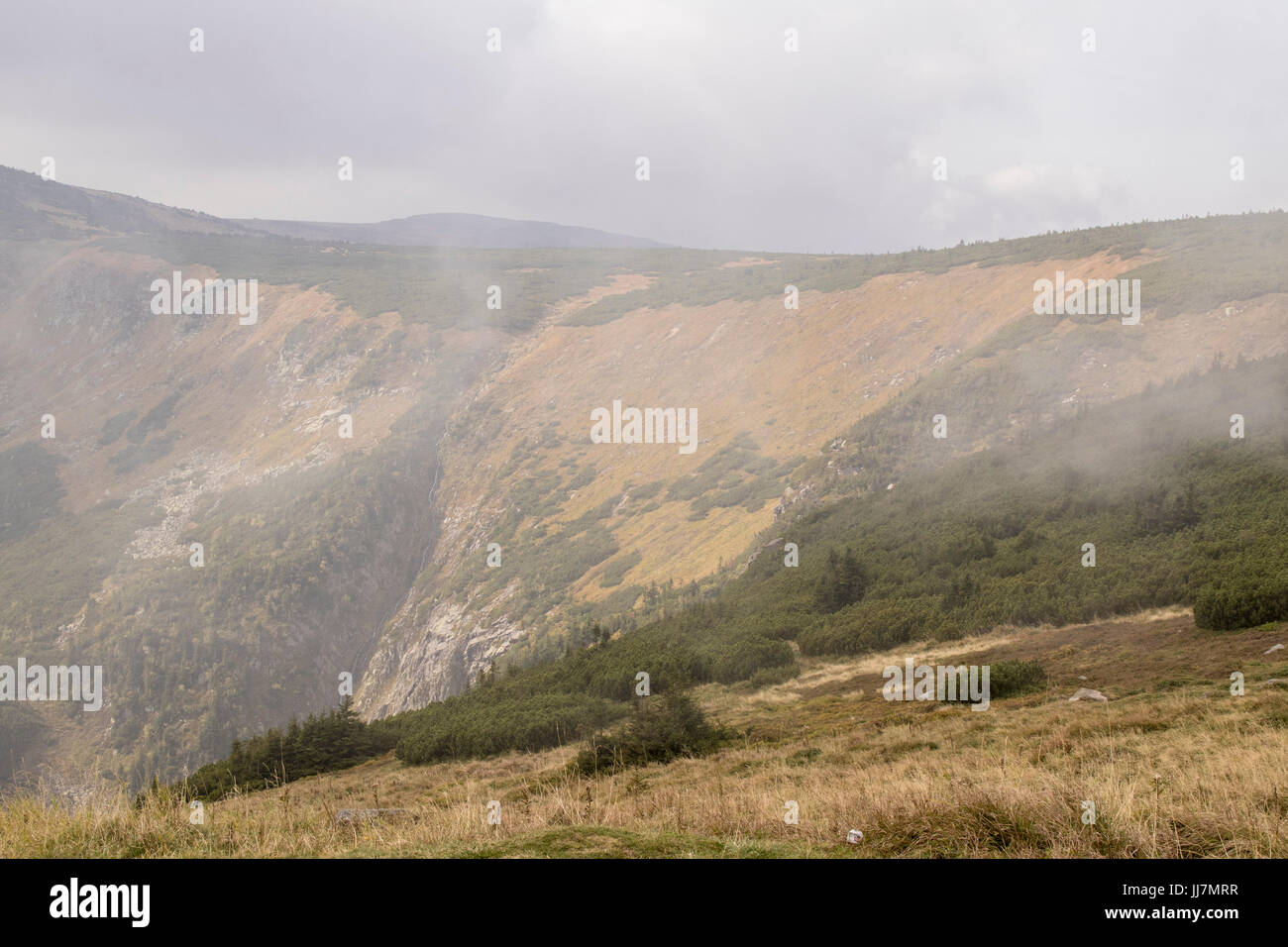 Autumn mountain lansdcape in overcast conditions taken from steep hill with foggy background Stock Photo
