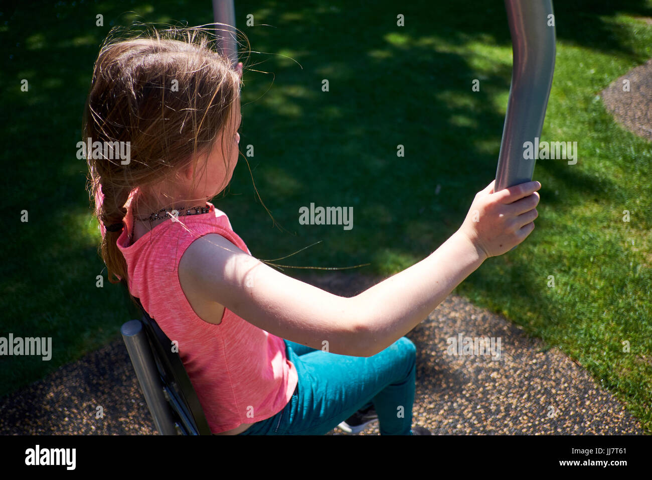 A young girl uses outdoor exercise equipment to exercise in a park on a sunny day - Stock Image