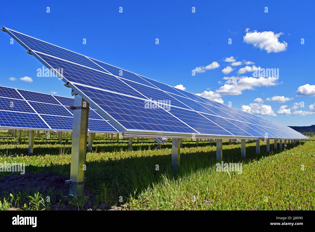 Solar panels on field. Clear sky with a few small clouds on background. - Stock Image