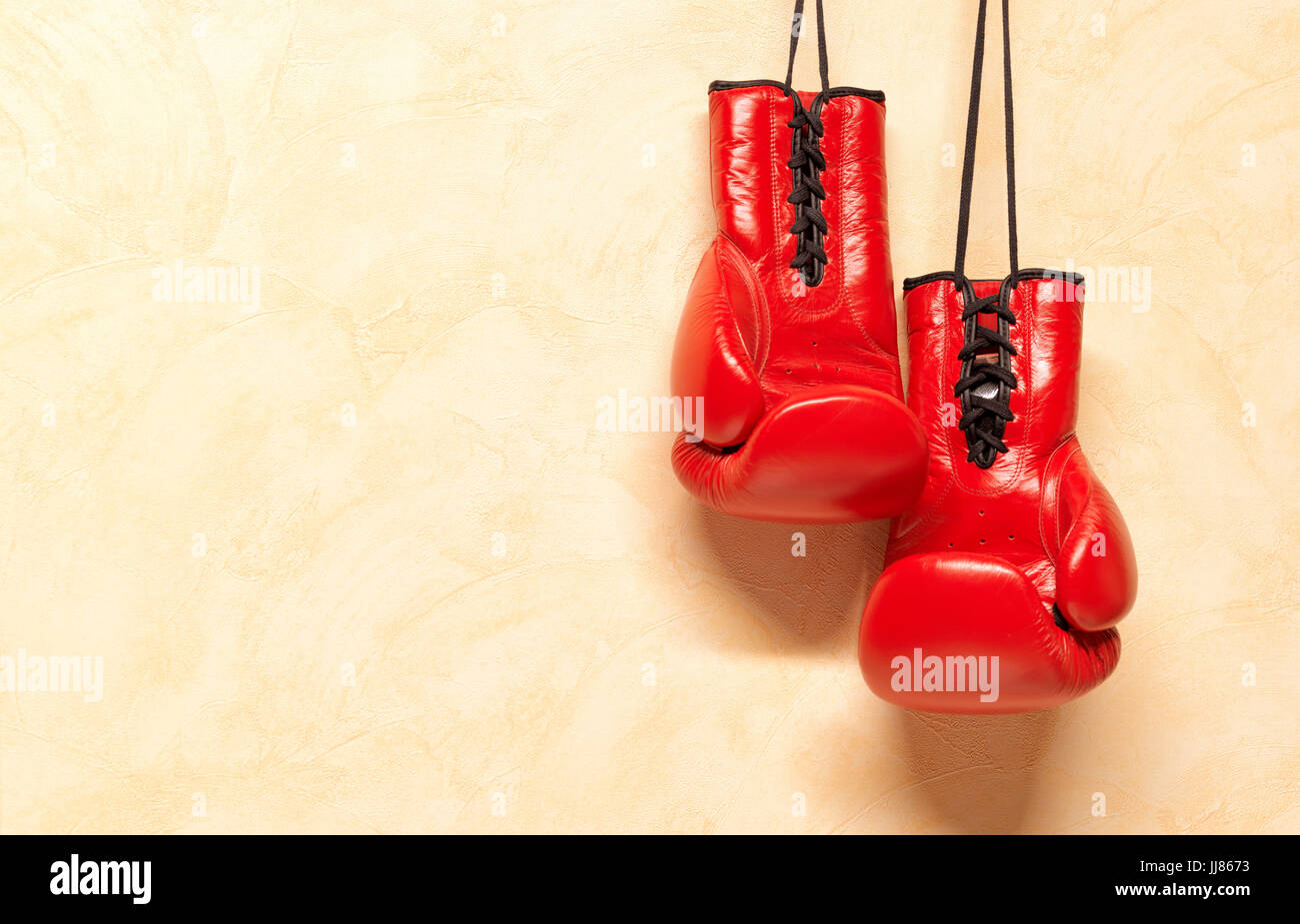 Red Boxing Gloves hanging by laces on Wall - Stock Image