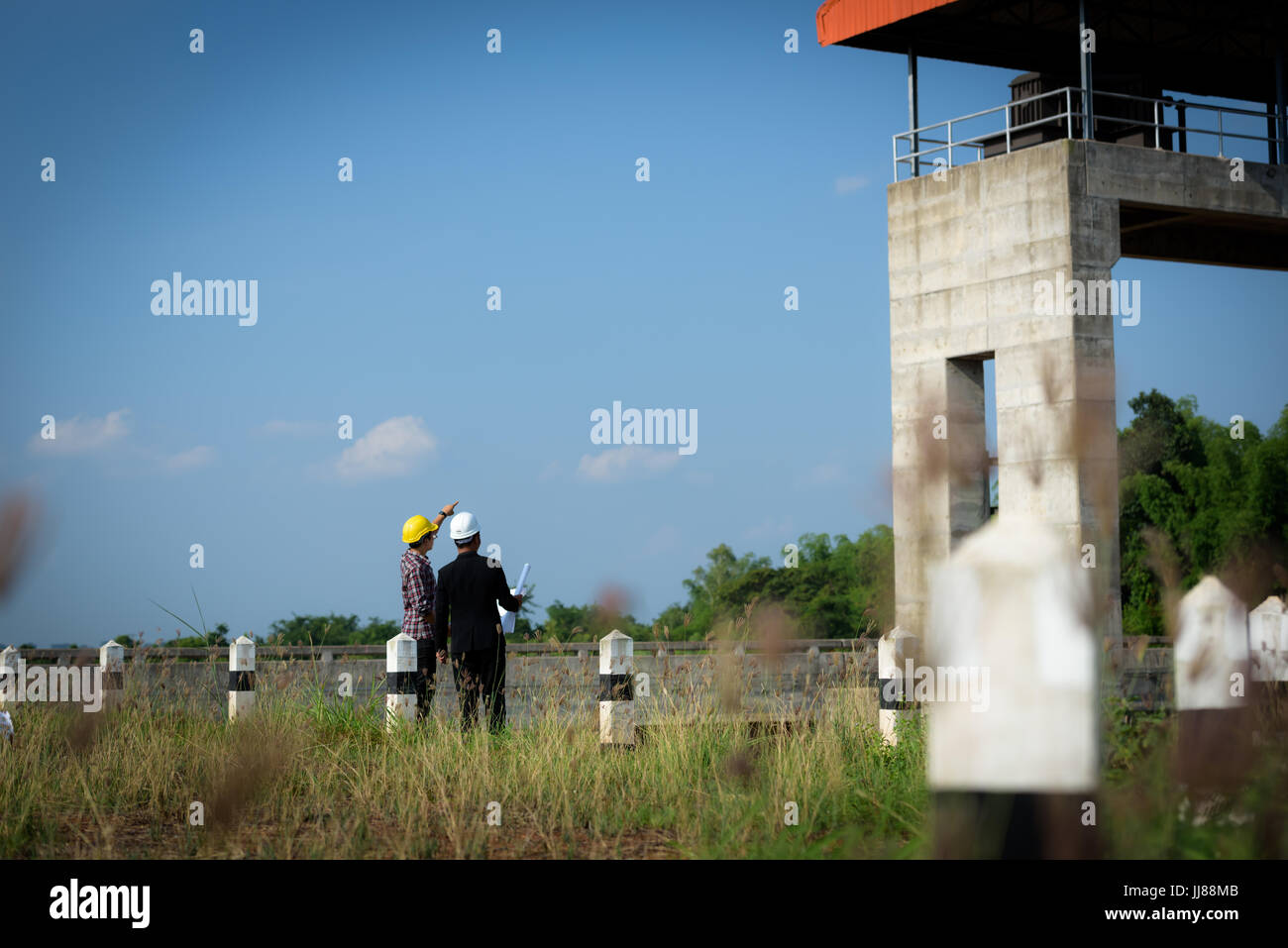 Business men meeting with Engineers and supervisors are standing reading the blueprints at the construction site. - Stock Image