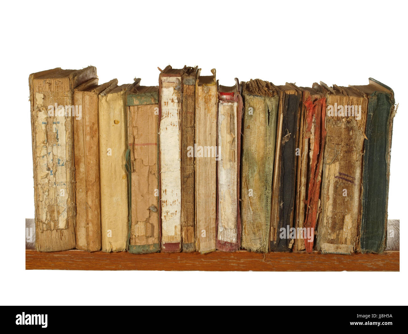 Very old and worn books on a wooden shelf isolated on white background. - Stock Image