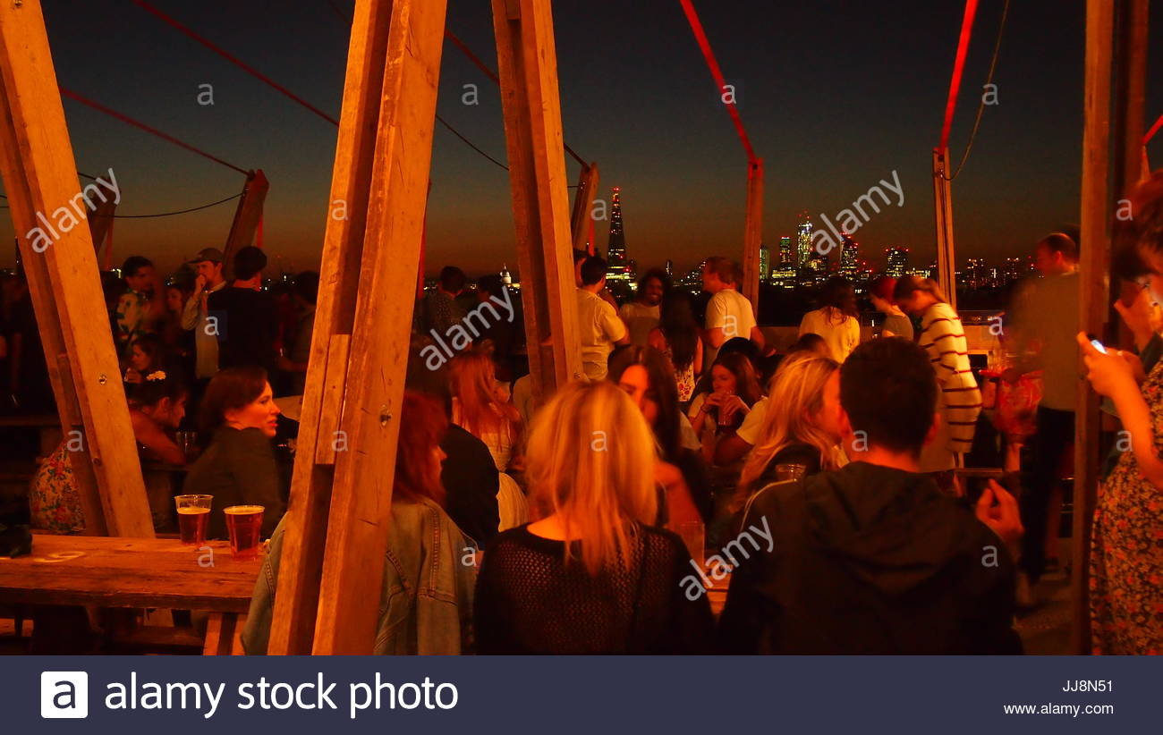 London, UK - 05 July 2013: A rooftop bar overlooking London's skyline on a warm summer night - Stock Image
