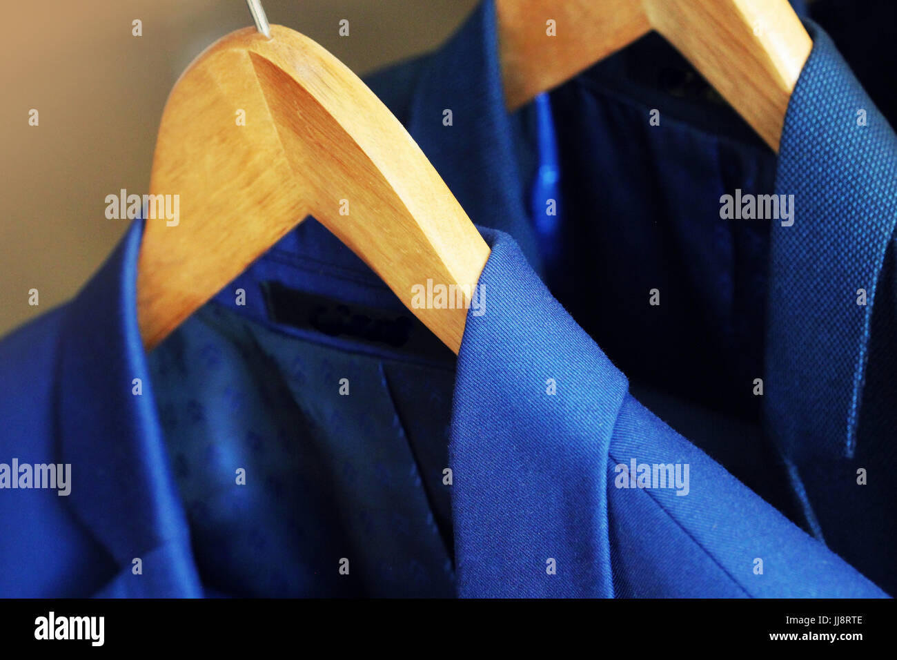 Row of men's suits hanging in closet - Stock Image