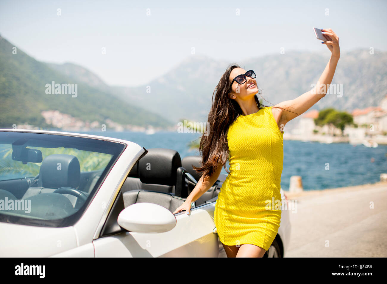 Pretty young woman in yellow dress taking selfie with mobile phone by white cabriolet car Stock Photo