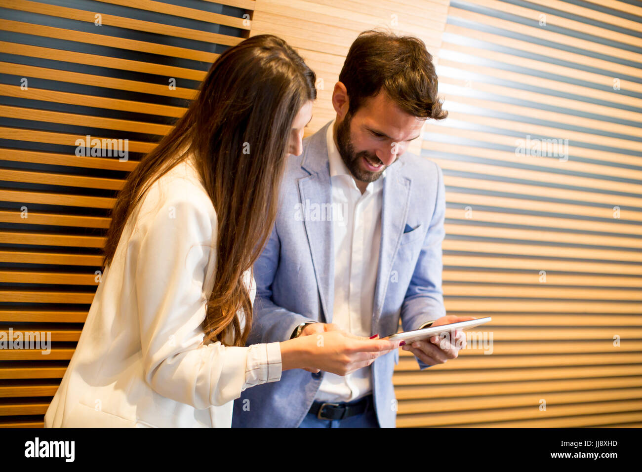 Young bussiness couple with tablet in the office - Stock Image
