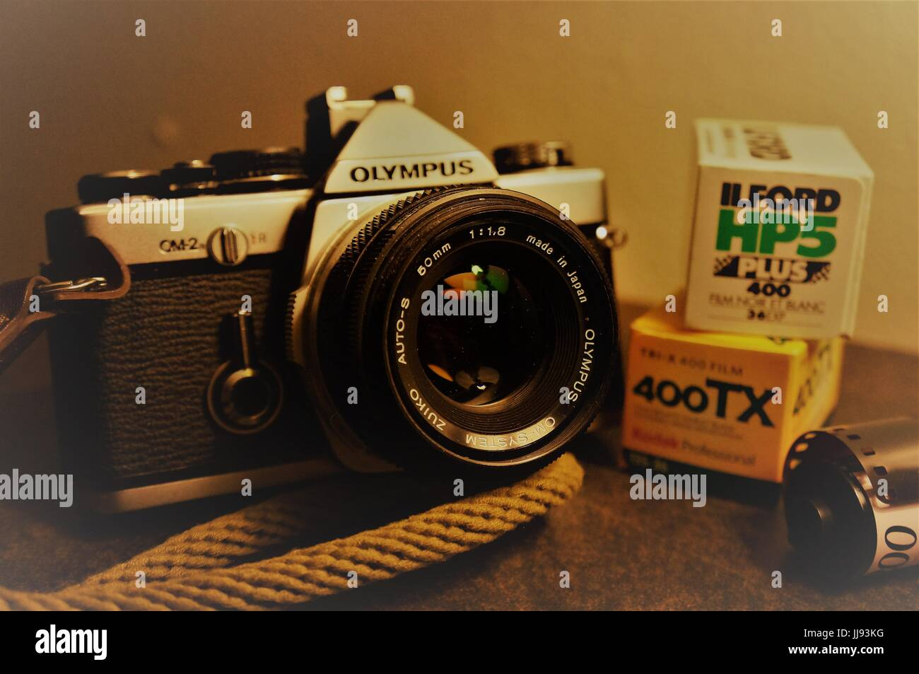 Vintage Olympus OM2n 35mm film camera with rolls of film - Stock Image