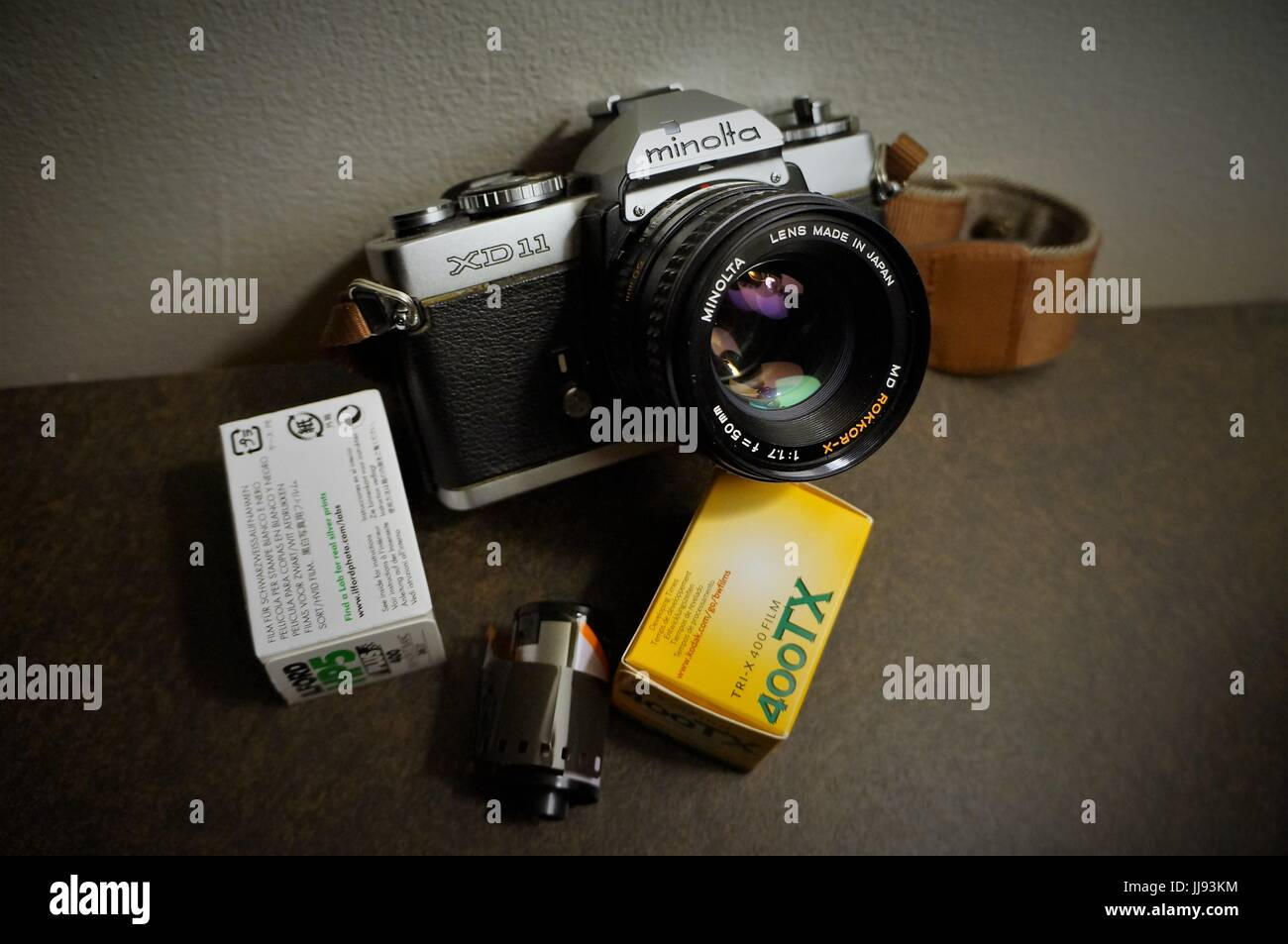 Minolta XD11 35mm camera with 50mm f1.7 lens and rolls of film - Stock Image