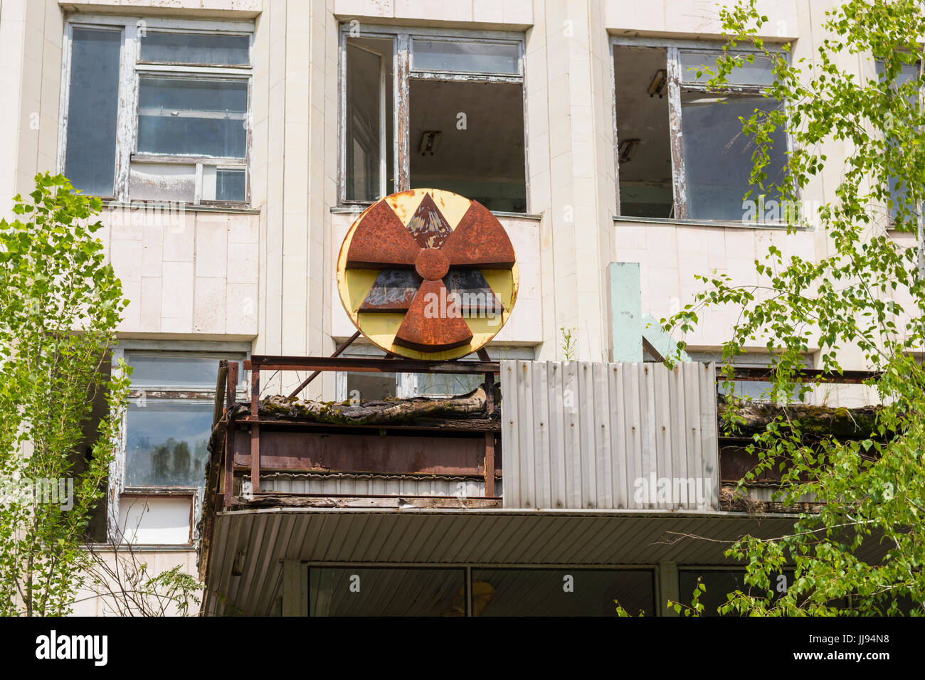 Radiation sign on building facade in ghost city of Pripyat in Chernobyl Exclusion Zone - Stock Image