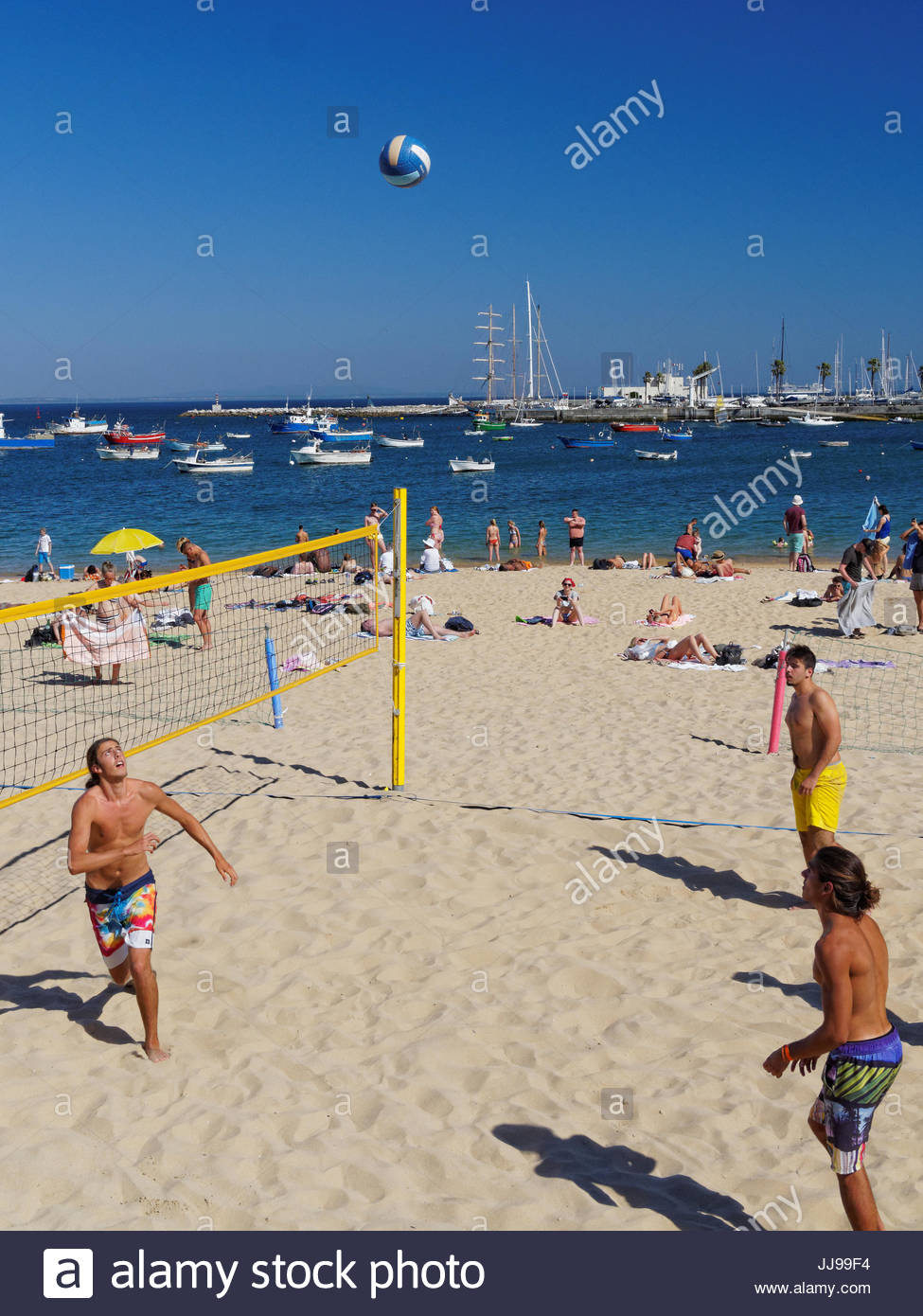 Three young men playing beach volley ball, Cascais, Portugal - Stock Image
