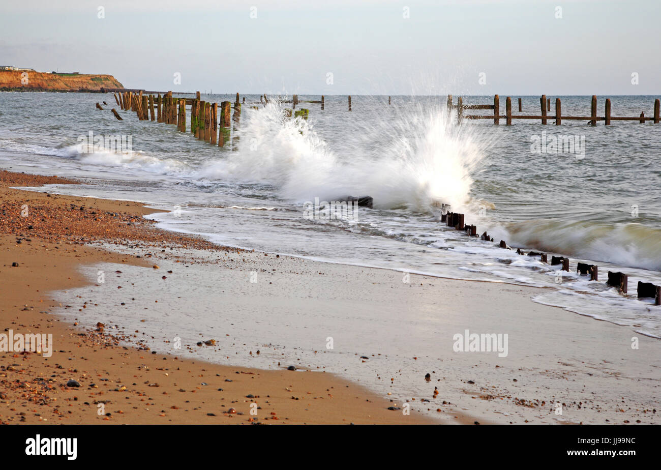 A view of the sea pounding old sea defences between Cart Gap and Happisburgh, Norfolk, England, United Kingdom. - Stock Image