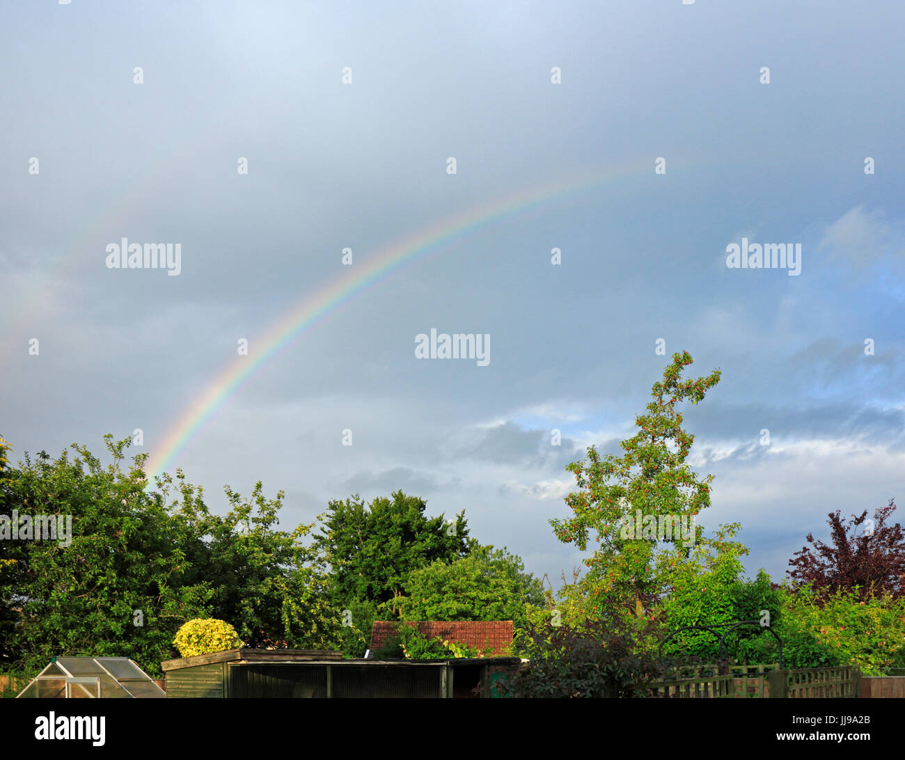 A view of a rainbow over gardens at Hellesdon, Norfolk, England, United Kingdom. - Stock Image