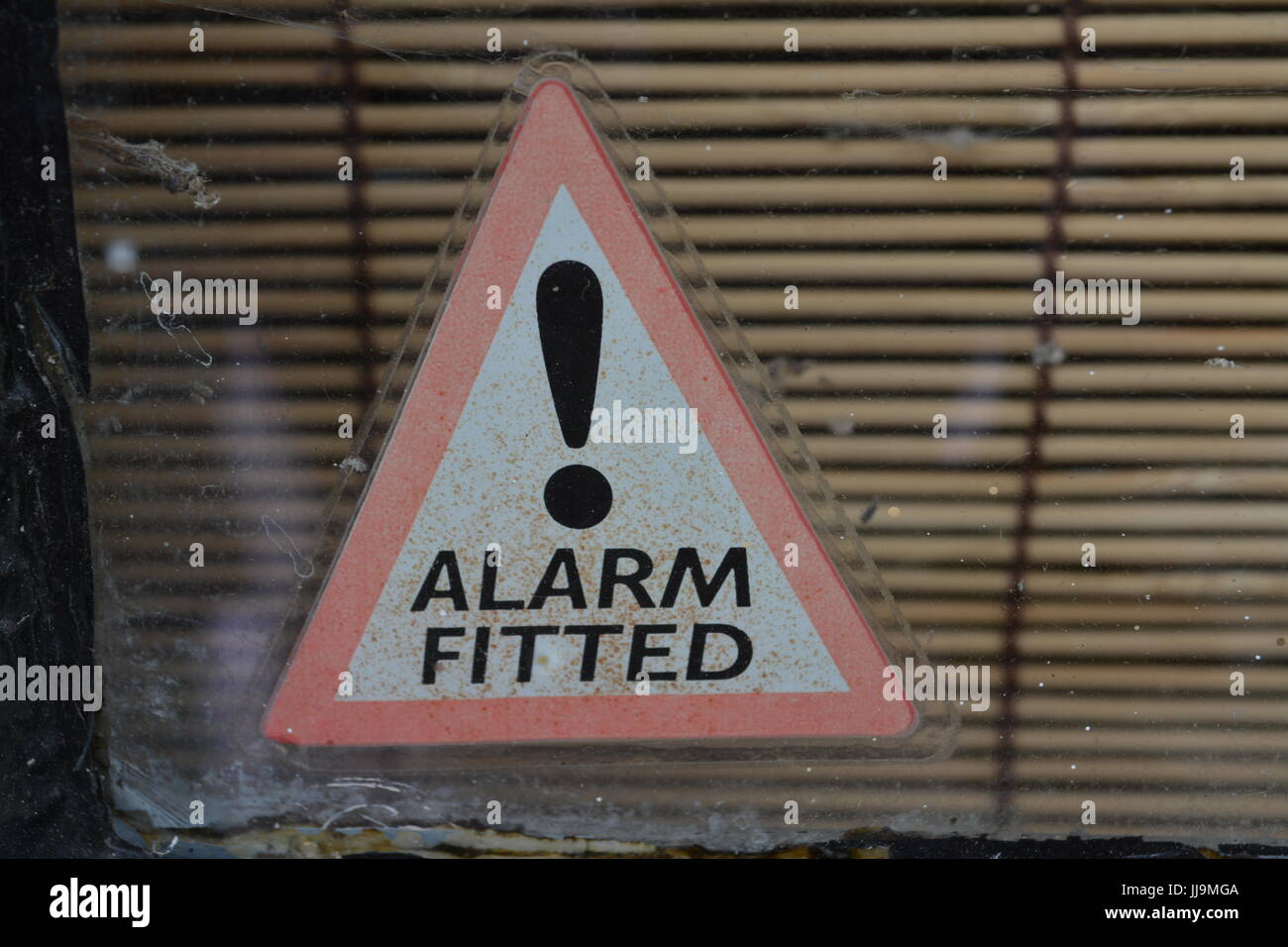 Alarm fitted triangular sign sticker on window glazing close up re warning sign house home security stop theft burglary - Stock Image