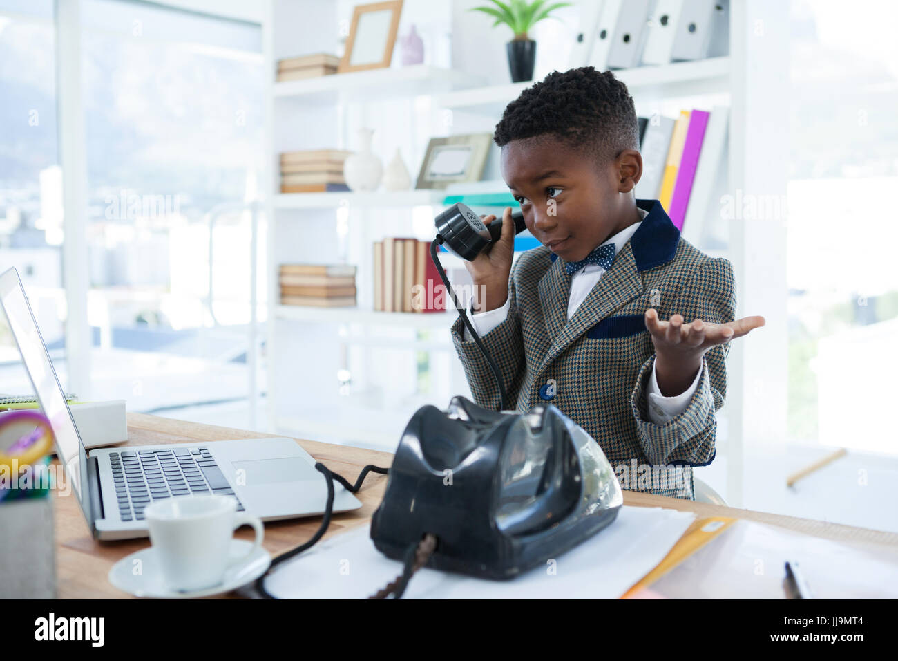 Businessman shrugging while talking on telephone at office desk - Stock Image